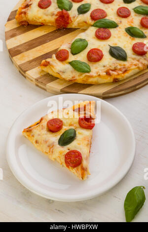 Coupe pizza margherita classique on white plate Banque D'Images