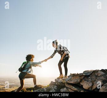 Amies à aider les uns les autres dans les montagnes. Young female hiker aider ami tandis que le trekking en montagne. Banque D'Images