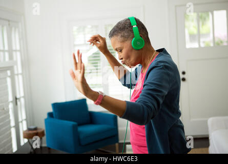 Senior woman listening to music on headphones Banque D'Images