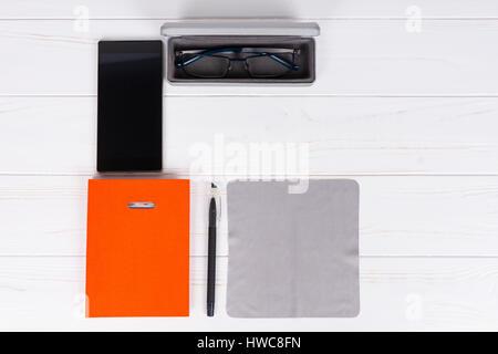 Journal Orange avec un stylo pour l'organisation d'un planning, verres en cas ouvert près de téléphone mobile sur Banque D'Images