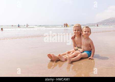 Mignon deux adorables petits frères garçons assis sur la plage Océan mer Banque D'Images