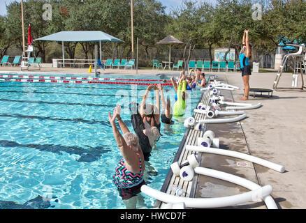 Groupe de femmes (tous âges) qui fréquentent l'eau aérobic, instructeur démontrant 'propre' exercice s'étendant Banque D'Images
