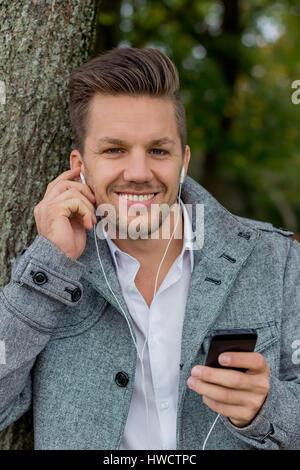 Un homme entend la musique avec votre téléphone mobile. Le divertissement sur le téléphone mobile., Ein Mann hört Musik mit Ihrem Handy. Unterhaltung suis Mobiltelefon.