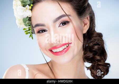 Portrait de femme avec des fleurs dans les cheveux à la recherche à l'appareil photo