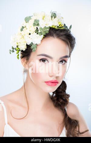 Portrait d'une femme avec des fleurs dans les cheveux on white