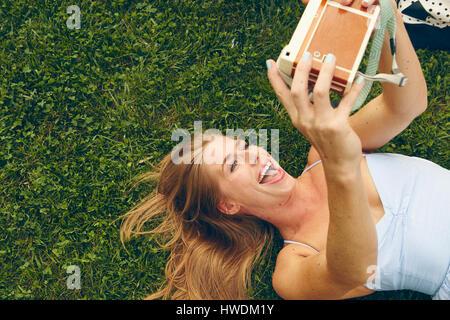 Young woman lying on grass en tenant l'appareil photo avec retro selfies Banque D'Images
