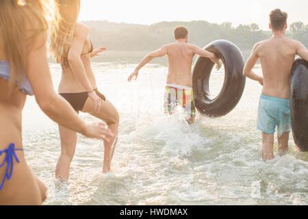 Les amis s'amusant avec anneau gonflable dans river Banque D'Images