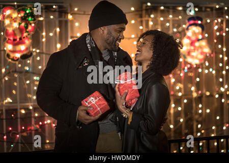 Romantic couple exchanging christmas gifts at night, New York, USA Banque D'Images