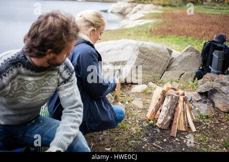 Homme recherche femme à couper du bois sur camping Banque D'Images