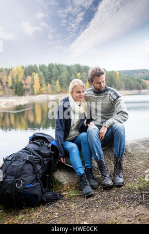 Sac à dos avec couple relaxing on lakeshore pendant camping Banque D'Images