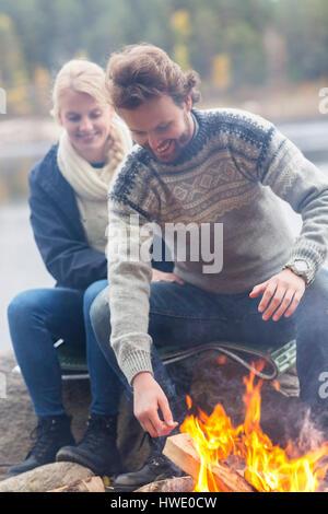 Heureux couple assis par feu sur Lakeshore Banque D'Images