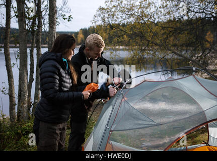 Jeune couple setting up tent by lake Banque D'Images