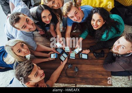 Vue d'en haut les mains à l'aide de cercle à cafe - téléphone mobile amis multiraciale dépendant du haut - scène Banque D'Images