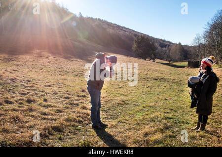 Man taking photo de femme et bébé garçon, à l'aide d'appareil moyen format, en milieu rural, Italie Banque D'Images