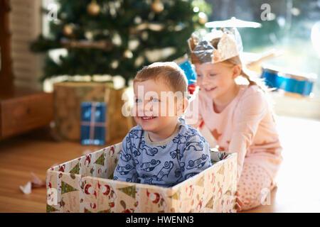 Fille frère poussant en boîte carton à Noël Banque D'Images