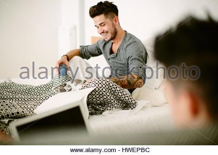 Homme couple de détente à la maison, boire du café, using laptop Banque D'Images