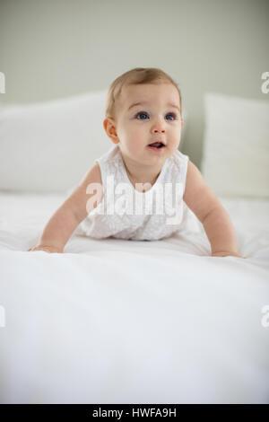 Portrait of cute smiling baby girl on lit dans la chambre Banque D'Images