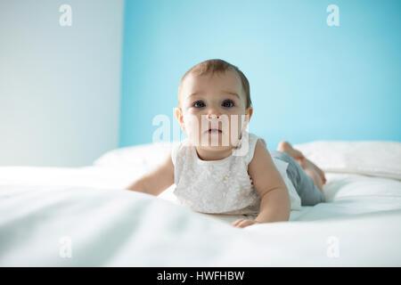 Portrait of cute baby girl on lit dans la chambre Banque D'Images