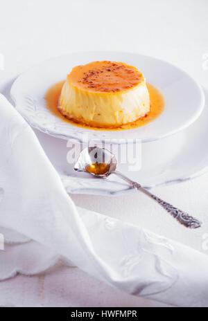 Crème caramel sur une assiette blanche servi sur une table