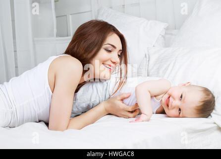 Heureux belle mère avec son fils âgé d'un an au lit à la maison Banque D'Images