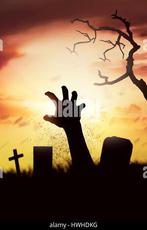 Les mains de relance cadavre Silhouette sa tombe sur le cimetière au coucher du soleil Banque D'Images