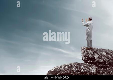 Image de musulman, homme debout sur le haut de falaise. En priant et en cherchant à le ciel Banque D'Images