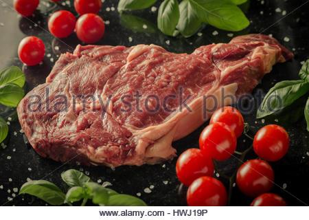 Steak frais servis avec des épices, les tomates et les feuilles de basilic sur en arrière-plan. Beefsteak cru avec Banque D'Images