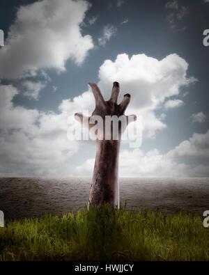 La main de Zombie qui sort de sa tombe. Concept d'Halloween Banque D'Images