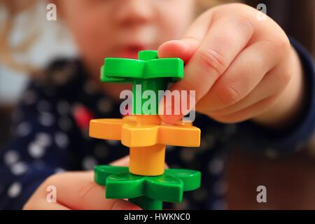 Kid construire tour constructeur avec close-up. Libre de constructeur dans les mains des enfants. Flou artistique Banque D'Images