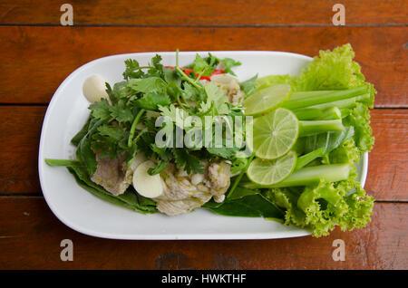 Porc bouilli avec de la chaux et de l'ail et de piment sauce citron épicé sucré appelé thai Moo Ma nao servi avec Banque D'Images