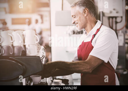Flare contre l'aide de machine à café barista heureux Banque D'Images
