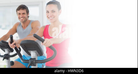 Smiling young couple working out at spinning class dans un bright gym Banque D'Images