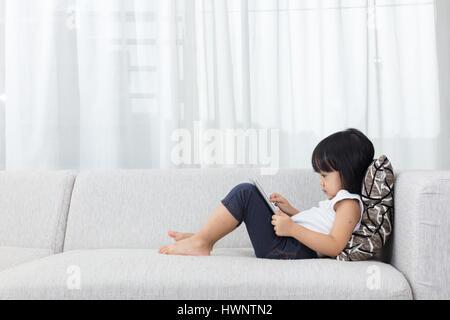 Chinois asiatique petite fille allongée sur le canapé avec tablette dans la salle de séjour à la maison