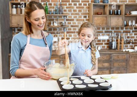 Portrait of smiling mother and daughter cooking cupcakes à la maison Banque D'Images