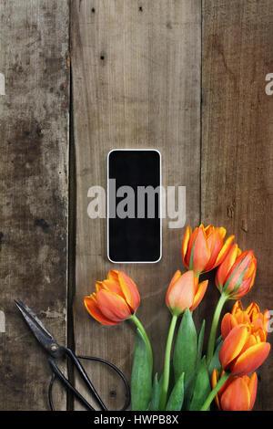 Passage tiré d'un téléphone cellulaire avec un bouquet de tulipes orange et jaune sur une table en bois rustique Banque D'Images