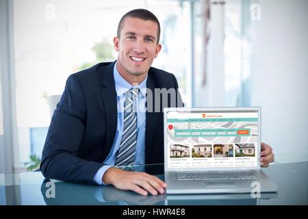 Portrait of smiling businessman montrant le portable contre les biens de l'image composite site web Banque D'Images