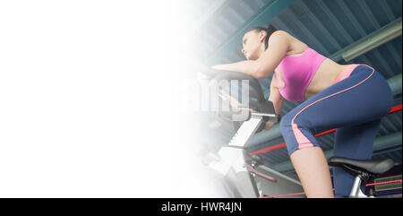Low angle view of a determined young woman working out at spinning class in gym Banque D'Images