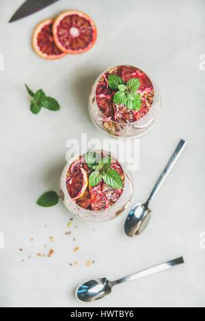 Petit-déjeuner sain avec yaourt, céréales, parfait en couches d'orange dans les verres Banque D'Images