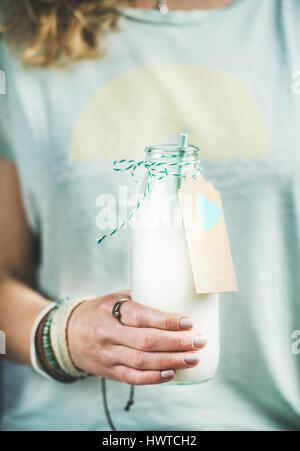 Jeune femme tenant une bouteille de lait d'amande sans produits laitiers Banque D'Images