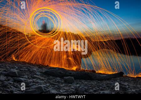 Une personne debout sur un rocher sur un lac au crépuscule la filature de la laine d'acier sur le feu avec des étincelles Banque D'Images