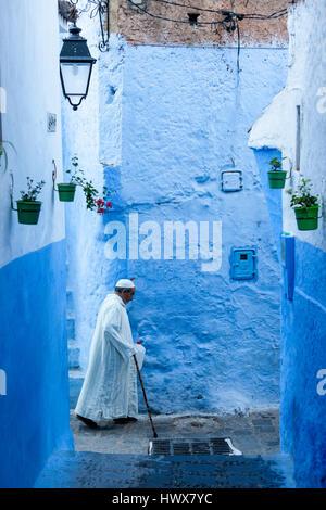Chefchaouen, Maroc. Homme marchant avec une canne dans une rue étroite.