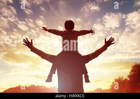 Temps de la famille père et fils watch et louer le coucher du soleil Banque D'Images