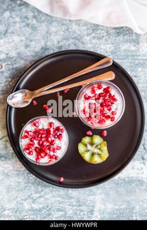 Deux verres de chia pudding avec des graines de grenade et de kiwis sur le bac Banque D'Images
