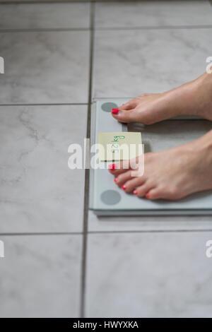 Femme debout sur un pèse-personne avec sticky note du poids idéal Banque D'Images