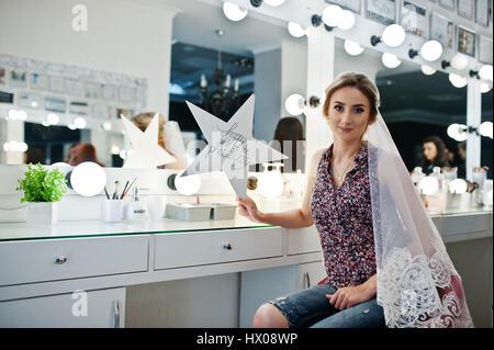 Jeune fille mariée assis sur une chaise près de miroir d'instituts de beauté et la tenue de star avec signe: les Banque D'Images