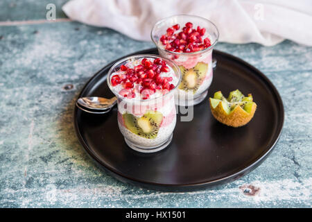 Deux verres de chia pudding en forme de cœur avec des tranches de kiwi et de graines de grenade sur le bac Banque D'Images
