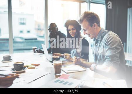 Groupe diversifié de gens d'affaires des jeunes adultes à répondre au pouvoir. Le café et les documents sur la table. Banque D'Images