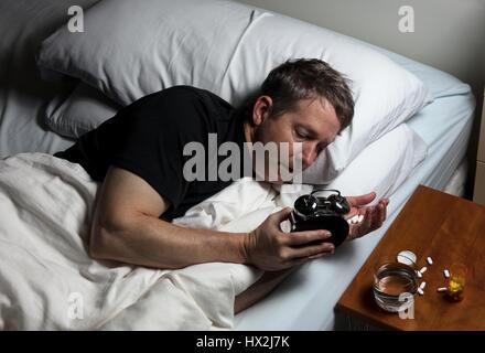Contrôle de l'homme mature temps sur réveil tout en se préparant à prendre des médicaments. L'insomnie concept. Banque D'Images