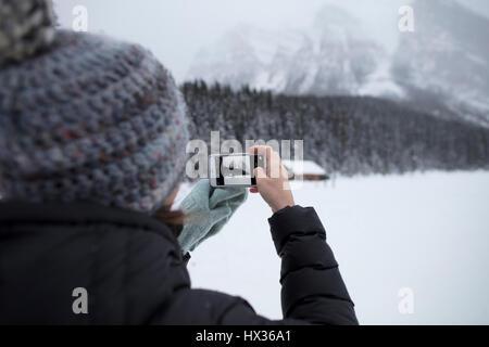 BANFF, ALBERTA, CANADA - Le 30 janvier 2017: un touriste prend une photo de la rivière Bow, près de l'hôtel Banff Banque D'Images