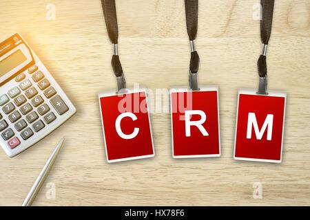 Gestion de la relation client ou CRM mot sur badge rouge avec lumière douce effet vintage